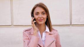Retrato da jovem mulher que fala no telefone celular e que olha a câmera vídeos de arquivo