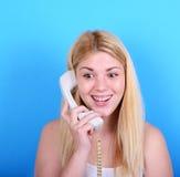 Retrato da jovem mulher que fala no telefone retro contra a parte traseira do azul fotografia de stock royalty free