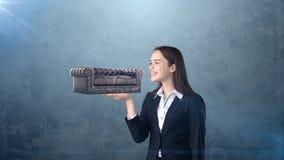 Retrato da jovem mulher que guarda o sofá 3D de couro na palma aberta da mão, sobre o fundo isolado do estúdio Conceito do negóci Fotografia de Stock Royalty Free