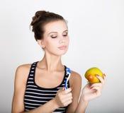 Retrato da jovem mulher que guarda uma maçã e uma escova de dentes, conceito dental da saúde imagens de stock