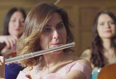 Retrato da jovem mulher que joga uma flauta Fotografia de Stock Royalty Free