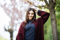 Retrato da jovem mulher que levanta perto de florescer a árvore de sakura fora imagens de stock royalty free