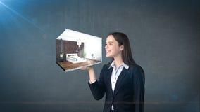 Retrato da jovem mulher que mantém 3d interior na palma aberta da mão, sobre o fundo isolado do estúdio Conceito do negócio Imagens de Stock Royalty Free