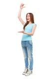 Retrato da jovem mulher que mostra algo grande com suas mãos Foto de Stock