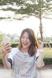 Retrato da jovem mulher que olha à tela do telefone celular com sur Foto de Stock
