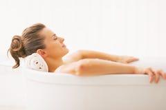 Retrato da jovem mulher que relaxa na banheira