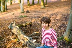Retrato da jovem mulher que senta-se e que relaxa na árvore caída na floresta outonal que olha a câmera, menina de sorriso outono imagens de stock royalty free
