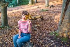 Retrato da jovem mulher que senta-se e que relaxa na árvore caída na floresta outonal que olha a câmera, menina de sorriso outono imagem de stock royalty free