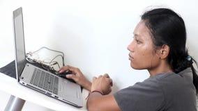 Retrato da jovem mulher que senta-se em uma tabela com portátil vídeos de arquivo