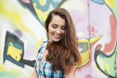 Retrato da jovem mulher que senta-se na parede dos grafittis Imagens de Stock Royalty Free