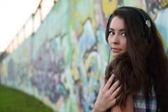 Retrato da jovem mulher que senta-se na parede dos grafittis Imagem de Stock Royalty Free