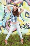 Retrato da jovem mulher que senta-se na parede dos grafittis Fotos de Stock
