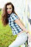 Retrato da jovem mulher que senta-se na parede dos grafittis Fotos de Stock Royalty Free