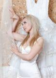 Retrato da jovem mulher que tenta sobre um vestido de casamento branco Fotografia de Stock Royalty Free