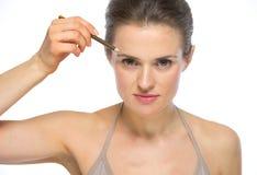 Retrato da jovem mulher que usa o lápis de sobrancelhas Foto de Stock Royalty Free