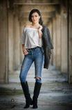 Retrato da jovem mulher 'sexy' bonita com equipamento moderno, casaco de cabedal, calças de brim, a blusa branca e as botas preta Fotografia de Stock Royalty Free