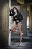 Retrato da jovem mulher 'sexy' bonita com equipamento preto, casaco de cabedal sobre a roupa interior, no fundo urbano Brunette a Imagem de Stock
