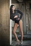 Retrato da jovem mulher 'sexy' bonita com equipamento preto, casaco de cabedal sobre a roupa interior, no fundo urbano Brunette a Fotografia de Stock
