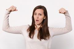 Retrato da jovem mulher surpreendida perplexo forte na roupa leve que mostra os bíceps, músculos isolados na parede branca imagem de stock royalty free