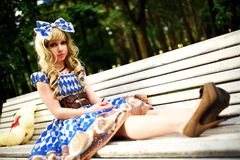 Retrato da jovem mulher vestido como a boneca que senta-se no banco Imagens de Stock Royalty Free