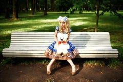 Retrato da jovem mulher vestido como a boneca que senta-se no banco Imagem de Stock