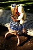Retrato da jovem mulher vestido como a boneca que senta-se no banco Fotos de Stock Royalty Free