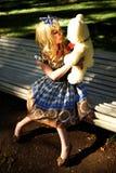 Retrato da jovem mulher vestido como a boneca que senta-se no banco Fotografia de Stock