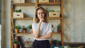 Retrato da jovem mulher da virada que olha a câmera e que expressa as emoções negativas que estão o estilo moderno interno do sót video estoque
