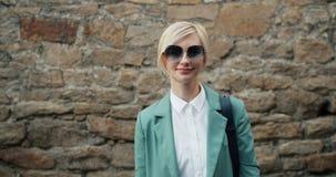 Retrato da jovem senhora bonita em óculos de sol à moda e na roupa moderna fora filme