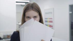 Retrato da jovem senhora brincalhão bonito na roupa formal que esconde sua cara atrás dos papéis que olham in camera e afastad video estoque
