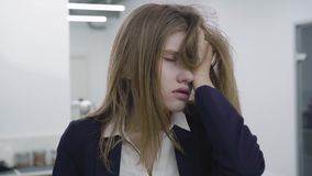 Retrato da jovem senhora cansado triste na roupa formal que agarra seu cabelo e olha afastado e para baixo, é decepcionada e filme