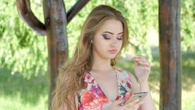 Retrato da jovem senhora relaxado em um parque do verão que lê uma mensagem de texto em seu telefone celular vídeos de arquivo