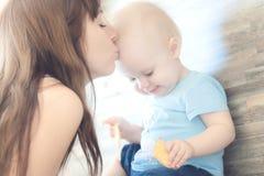 Retrato da mãe bonita que beija sua menina da criança fotografia de stock royalty free