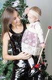 Retrato da mãe com a filha perto da árvore de Natal Fotografia de Stock Royalty Free