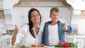 Retrato da mãe de sorriso nova da família feliz e do filho bonito que mostram os polegares frescos do gesto acima video estoque