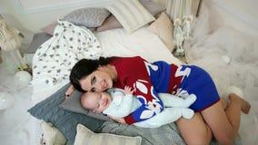 Retrato da mãe e do bebê, jovem mulher que afaga, aperto, acariciando seu filho novo, família em uma casa confortável video estoque