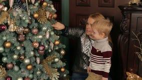 Retrato da mãe e do filho perto da árvore de Natal video estoque
