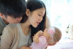 Retrato da mãe e do pai novos com o recém-nascido na sala da cama, fá fotos de stock royalty free
