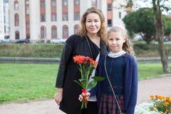 Retrato da mãe e da estudante que vão para trás à escola, flor da terra arrendada da filha imagem de stock