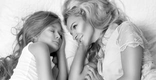 Retrato da mãe e da filha louras bonitas da mulher na cara bonita e mentira surpreendente dos olhos que dormem em uma cama em um  Imagem de Stock Royalty Free