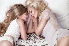 Retrato da mãe e da filha louras bonitas da mulher na cara bonita e mentira surpreendente dos olhos que dormem em uma cama em um  Imagens de Stock