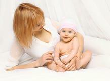Retrato da mãe feliz com o bebê que encontra-se junto na cama Imagem de Stock Royalty Free