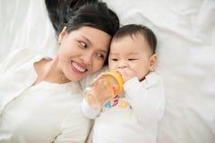 Retrato da mãe feliz e do bebê asiáticos que têm o divertimento junto em casa na sala branca Fotos de Stock Royalty Free
