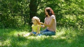 Retrato da mãe moreno que faz seu penteado pequeno da filha que senta-se na grama verde no parque video estoque