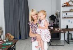 Retrato da mãe nova bonita que guarda a filha pequena nas mãos imagens de stock royalty free