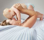 Retrato da mãe nova feliz que abraça o bebê bonito fotografia de stock royalty free