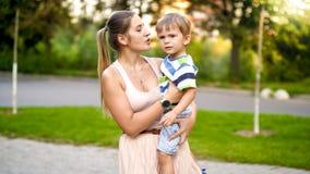 Retrato da mãe nova que abraça seus 3 anos do filho pequeno idoso e que fala a ele ao andar no parque imagem de stock