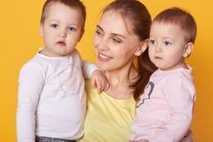 Retrato da mãe nova que guarda seus gêmeos pequenos, infantes ativos bonitos que estão sendo interessados para ser photografed, a imagens de stock