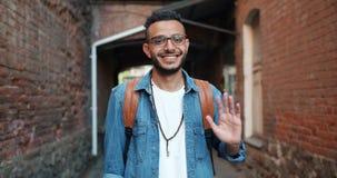 Retrato da mão de ondulação do homem árabe alegre amigável que sorri fora video estoque