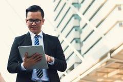 Retrato da mão nova moderna segura do terno do preto do desgaste do homem de negócios que guarda a tabuleta digital Homem de negó foto de stock